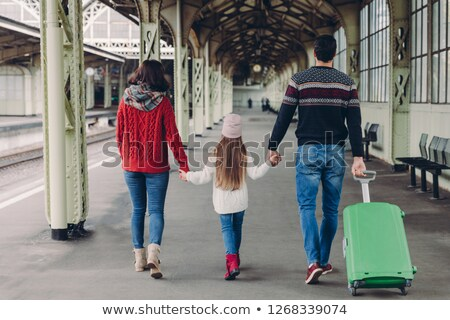 Back view of friendly family hold hands, carry suitcase, going to have voyage trip, pose on railway  Stock photo © vkstudio