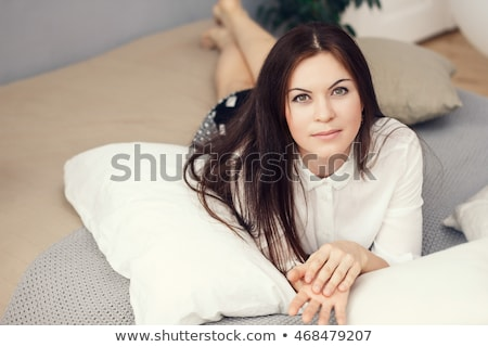 Happy adult woman lying on pillows and enjoying serenity and comfort Stock photo © dashapetrenko