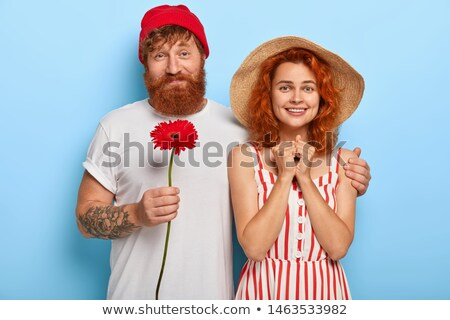 Photo of lovely ginger female with satisfied expression, holds sunglasses, has spare time, sits in o Stock photo © vkstudio