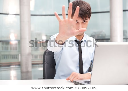 angry young businessman sitting at his desk and showing stop ges stock photo © hasloo