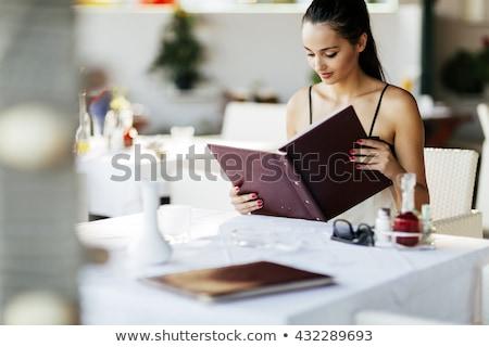 woman looking at the menu at a restaurant Stock photo © photography33