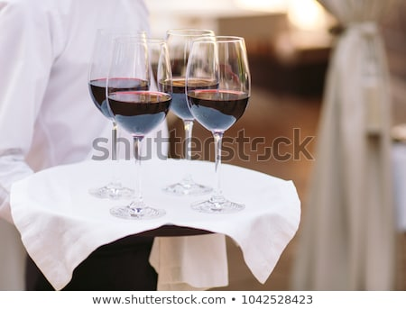 Waiter holding bottle of wine and glasses on tray Stock photo © photography33
