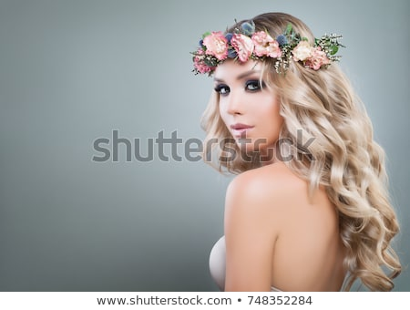 Beautiful young lady with flower and leaf  in her hair Stock photo © Elmiko