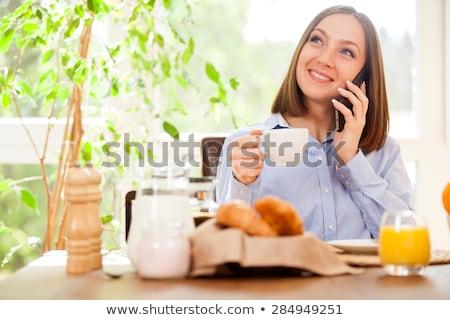 Mujer desayuno teléfono mujer sonriente cocina casa Foto stock © wavebreak_media