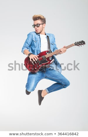 Stock fotó: Male Artist Jumping In Studio While Playing Guitar