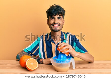 Friends looking at fresh fruits in the juicer Stock photo © Kzenon