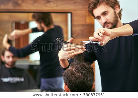 barber cutting hair with scissors. back view of man in barber shop Stock photo © ruslanshramko