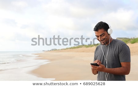 Handsome young guy walking outdoors listening music with earphones. Stock photo © deandrobot