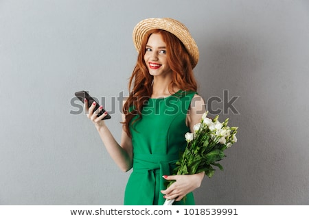 redhead woman holding flower looking camera stock photo © deandrobot