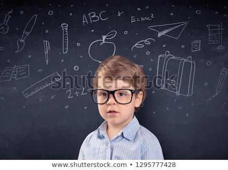 Little boy in front of a drawn up blackboard Stock photo © ra2studio
