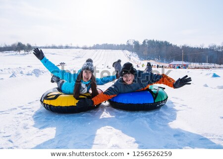happy friends sliding down hill on snow tubes Stock photo © dolgachov