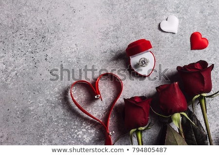 Red ribbon and jewel on red background Stock photo © nurrka