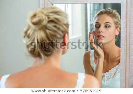 Stock photo: young woman looking at her reflection in a bathroom mirror