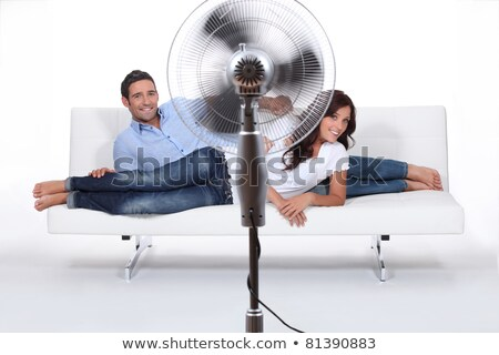 Man and woman laid on a sofa being ventilated by fan Stock photo © photography33