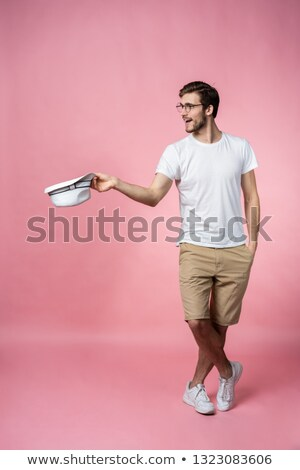 happy attractive young man holding hat and asking for money stock photo © deandrobot