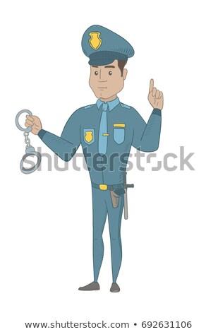Young hispanic policeman holding handcuffs. Stock photo © RAStudio