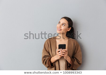 portrait of a cheerful smiling woman texting stock photo © deandrobot
