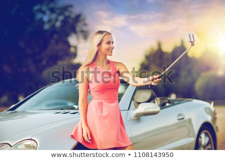 woman in convertible car taking selfie over sunset Stock photo © dolgachov