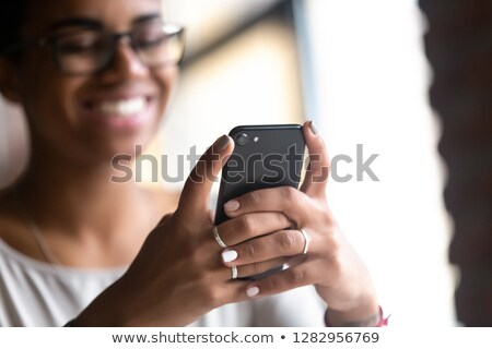 photo of cheerful african american students holding and reading stock photo © deandrobot