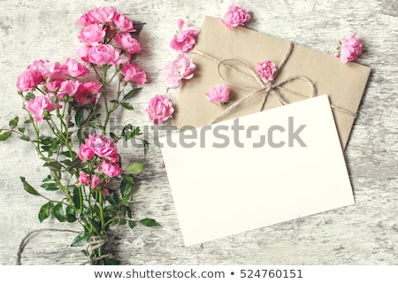 Card for congratulation with envelope and fresh flowers on a light turquoise background. Stock photo © artjazz