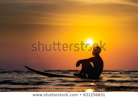 silhouette of surf man sitting with a surfboard on the seashore beach at sunset time banner long fo stock photo © galitskaya