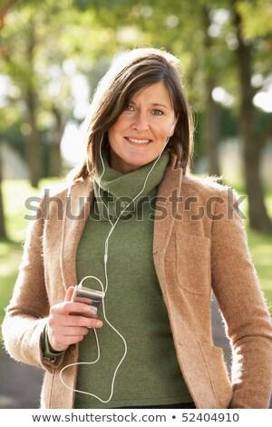 Сток-фото: женщину · прослушивании · mp3 · ходьбе · осень · парка