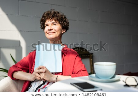 Pretty young woman with open book or notebook getting inspired on sunny day Stock photo © pressmaster