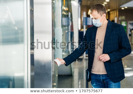 Man protects hands from direct contact with door handle, uses paper napkin from conntracting virus t Stock photo © vkstudio
