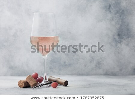 Glass of white homemade wine with corks, corkscrew and grapes on wooden board with linen cloth on li Stock photo © DenisMArt