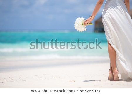 Young bride on the beach wqith flowers stock photo © Massonforstock