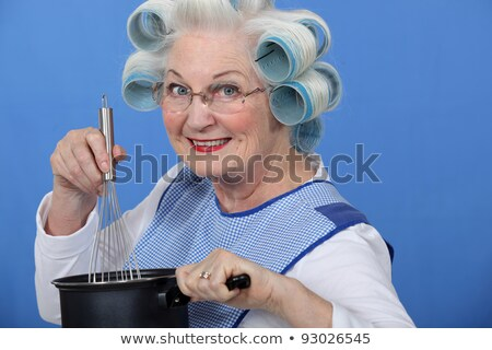 Stock photo: Granny cooking with her hair in rollers