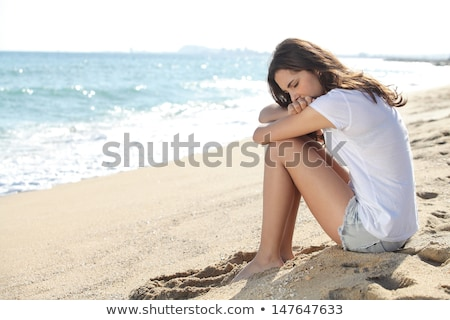 sad brunette woman sitting on beach stock photo © chesterf