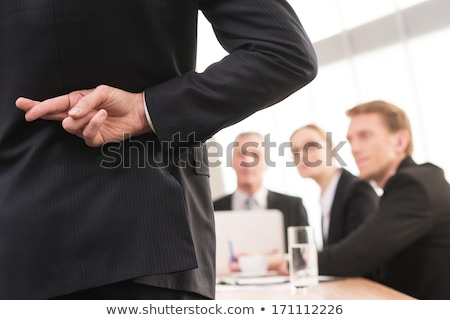 Smiling businessman with fingers crossed behind his back Stock photo © Paha_L