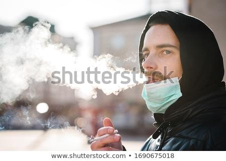 Smoking man with mask Stock photo © badmanproduction