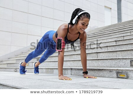 relaxed african american sportswoman listening to music from mobile phone stock photo © deandrobot