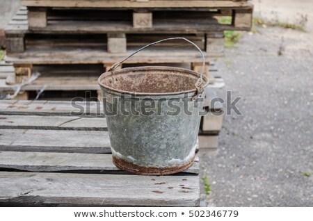 an old iron bucket at wooden pallet Stock photo © Valeriy