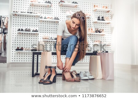 Pretty young woman trying on new sunglasses Stock photo © deandrobot