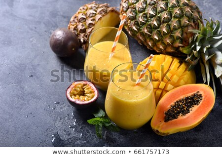 Juicy ripe tropical fruits, pineapple, papaya, mango, pineapple, green palm leaves and empty round p Stock photo © artjazz