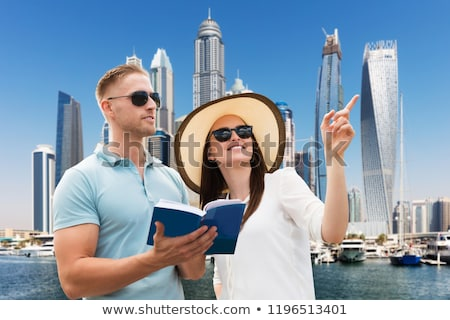 woman showing direction to her husband holding guide book stock photo © andreypopov