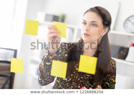 A young girl stands near a transparent board with stickers and holds a glass with coffee and a marke Stock photo © Traimak
