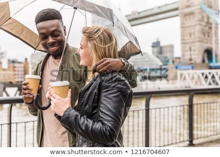 couple walking together with umbrella stock photo © kzenon