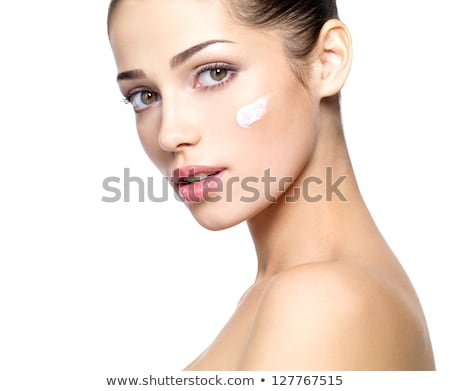 Beautiful face of young woman with cosmetic cream on a cheek Stock photo © serdechny