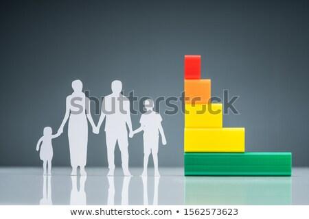 White Family Paper Cutout Near Graph On Reflective Desk Stock photo © AndreyPopov
