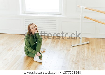 Photo of professional female dancer has rest after training, poses on floor near ballet barre, has b Stock photo © vkstudio
