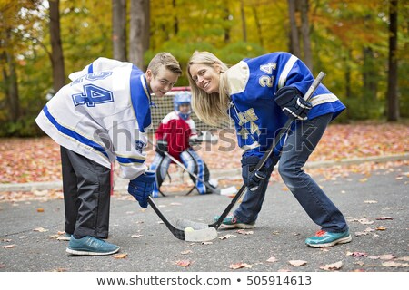 portrait of happy child play hockey outside with mother Stock photo © Lopolo