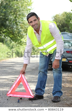 Man in fluorescent vest putting out a warning triangle by a breakdown Stock photo © photography33