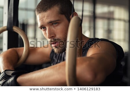 Crossfit dip ring man relaxed after workout at gym dipping Stock photo © lunamarina