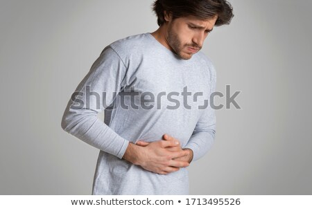 Young man suffering from a bad stomach ache pain isolated on whi Stock photo © dacasdo