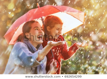 girl with an umbrella in the rain playing with mom Stock photo © koca777