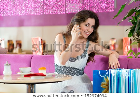 Young woman in ice cream parlor with phone texting Stock photo © Kzenon